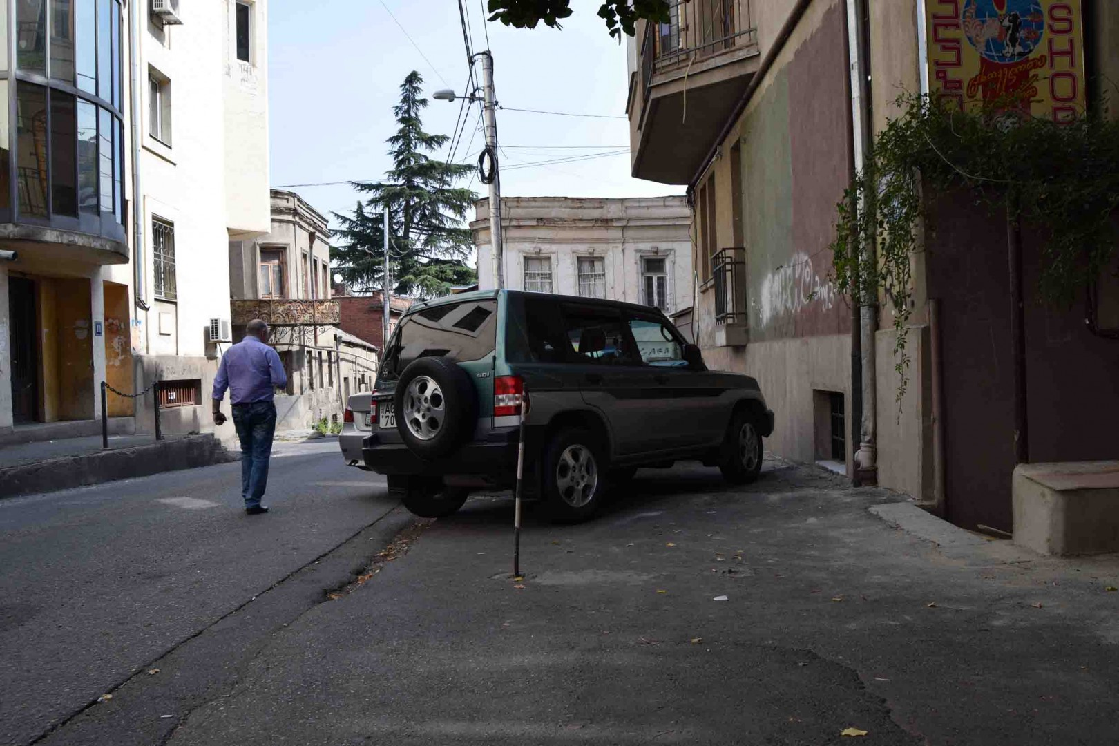 The photo clearly shows that pedestrians are forced to use machinery road, because the sidewalk is completely occupied by the cars. Lado Asatiani street. Tbilisi old town.